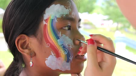 prenses : A cute 11 year old Asian girl gets clouds added to her rainbow face painting design.