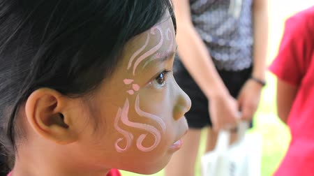 prenses : A cute little 7 year old Asian girl gets a pretty face painting design done on her face. Stok Video