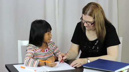 домохозяйка : A pretty woman teaching her cute Asian daughter during a homeschool lesson at home.