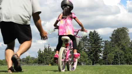 hrdý : An excited dad celebrates her young Asian daughter ride her pink bike without training wheels for the first time.