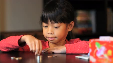 empilhamento : A cute little six year old Asian girl counts up her money.