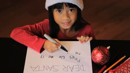 świety mikołaj : A happy six year old Asian girl writes a special letter to Santa Claus at Christmas. Wideo