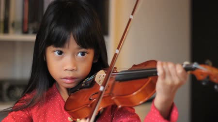 küçük kız : An intense little 6 year old Asian girl plays her violin in the living room. Stok Video