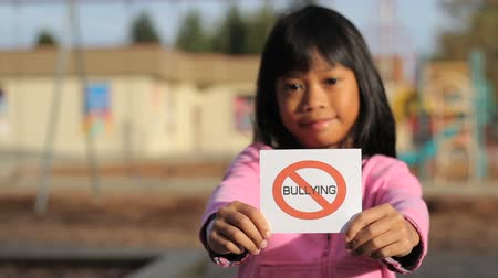 abuso : A cute Asian girl holds up a NO BULLYING sign in front of a school. Stock Footage