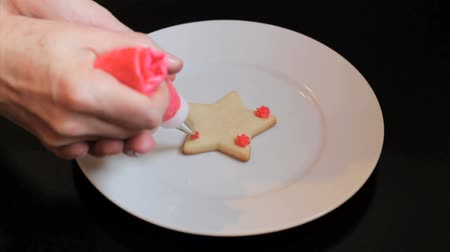 pişmiş : A girl carefully decorates a star shaped shortbread Christmas cookie with red icing. Stok Video