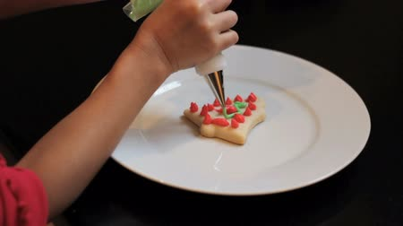 pişmiş : A 5 year old Asian girl carefully adds green icing to her bell shaped shortbread Christmas cookie.