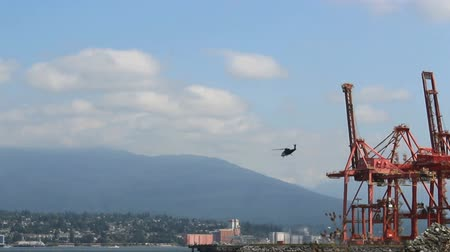 heliport : A helicopter takes off and flies across the Burrard Inlet in Vancouver, BC.