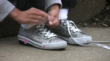 koronka : A little Asian girl learns to tie her shoe laces on her new sparkly shoes. Wideo