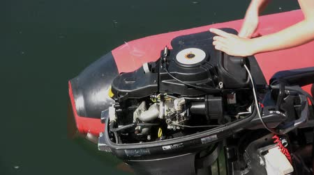 csavarkulcs : A woman using a ratchet wrench trying to fix an outboard motor. Stock mozgókép