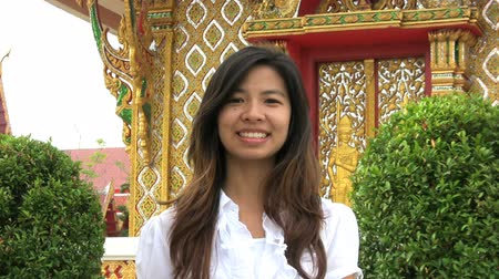 cortes : An Asian girl doing a Thai style greeting in Bangkok, Thailand.