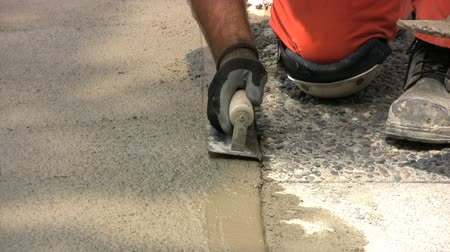 kielnia : A construction worker finishes troweling a sidewalk in the downtown area.