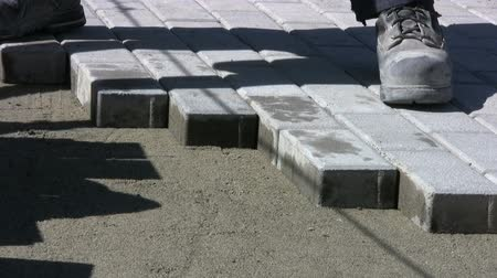 empilhamento : A worker patiently installs interlocking sidewalk bricks on a sunny day. Stock Footage