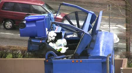 mal cheiroso : A recycling garbage truck dumps a new load of recyclables into its bins.