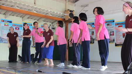 ratchaburi : A group of cute Asian students and a foreign youth missions team have fun dancing during a school assembly in Ratchaburi, Thailand.