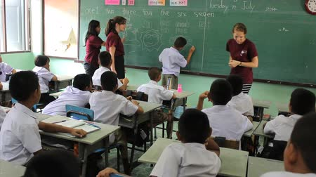 İngilizce : A young Asian student volunteers to come to the board to draw his drawing during a short-term missions English class in Ratchaburi, Thailand. Stok Video