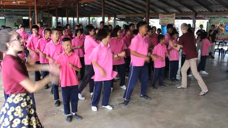 ratchaburi : A group of cute Asian students have fun dancing during a school assembly in Ratchaburi, Thailand.