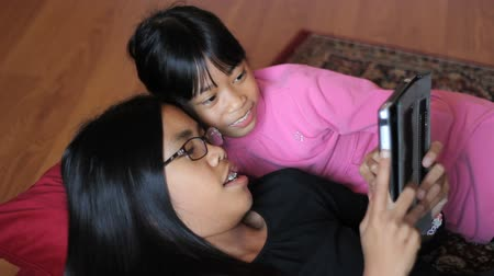 touchpad : Two cute Asian sisters enjoy spending time together playing on their new digital tablet in the living room. Stock Footage