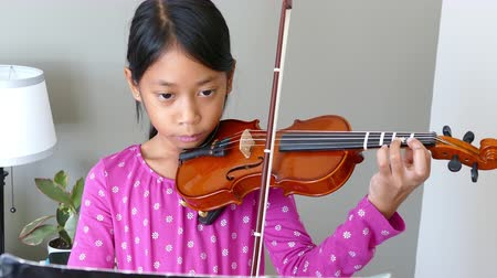 houslista : A cute little 9 year-old Asian girl diligently practices her violin in her bedroom.