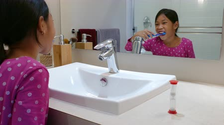 зубы : A cute little 9 year old Asian girl uses an egg timer to help her brush her teeth longer.