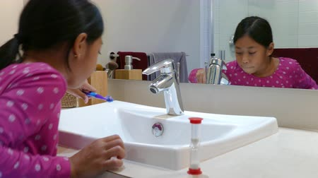 escovação : A cute little 9 year old Asian girl uses an egg timer to help her brush her teeth longer.