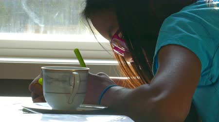 yazarak : A cute 13 year old Asian girl spends time drawing on the kitchen table while enjoying a sunbeam.