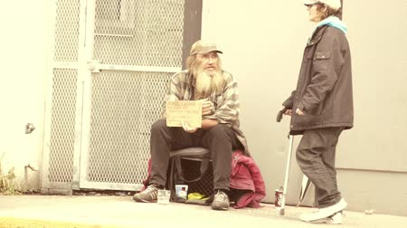 tek başına : VANCOUVER, BC, OCTOBER 2015: A person using a cane walks past an old homeless man living on the streets of Vancouver, BC. Stok Video