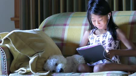 touchpad : A cute little Asian girl uses her tablet alone in the living room with her faithful puppy at her side. Stock Footage
