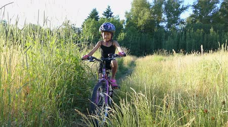 kolo : A cute 9 year old Asian girl rides her new bike through a grassy field on a beautiful summer evening. Dostupné videozáznamy