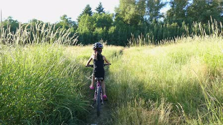 kask : A cute 9 year old Asian girl rides her new bike through a grassy field on a beautiful summer evening. Stok Video