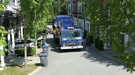 lixo : A new modern garbage truck comes to collect the trash in a suburban townhouse community. Stock Footage