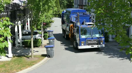 hidrolik : A new modern garbage truck comes to collect the trash in a suburban townhouse community. Stok Video