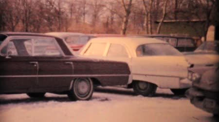 ploutve : A man drives his Cadillac into a crowded snowy parking lot in the winter of 1963.