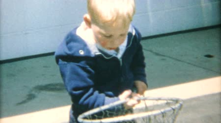 żart : A cute little blond haired boy spends time fishing in his driveway with his new fishing net in the summer of 1967.