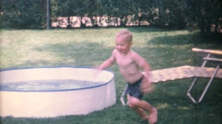 szőke : A cute little blond haired boy enjoys jumping and diving and splashing in his new kiddie pool in the back yard in 1967. Stock mozgókép