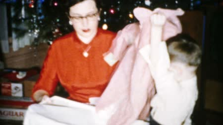 A woman in a bright red dress gets a brand new pink jacket for Christmas in Cleveland, Ohio in 1956. Stock mozgókép