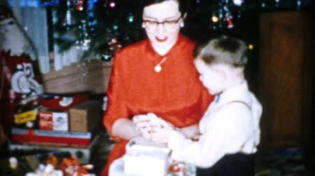 A pretty mother spends time with her excited son opening gifts and celebrating Christmas in Cleveland, Ohio in 1956.