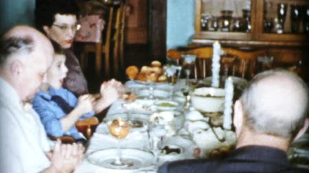 A family prays and gives thanks to God for the turkey dinner while  celebrating Christmas in Cleveland, Ohio in 1956. Wideo