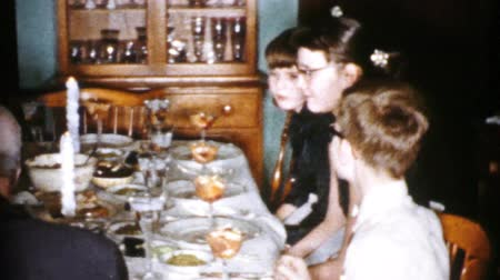A family enjoys spending time eating a delicious turkey dinner while celebrating Christmas in Cleveland, Ohio in 1956.