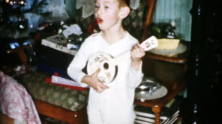 A cute little boy enjoys playing his new guitar and singing songs on Christmas morning in Cleveland, Ohio in 1956. Stock mozgókép