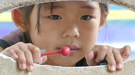hill tribe : A cute little Asian hill tribe girl peeks at the action inside the community center being too fearful to go inside, in Chiang Rai, Thailand. Stock Footage