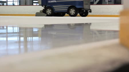 skate : An ice making machine cruises by on the ice rink cleaning the surface for new skaters.