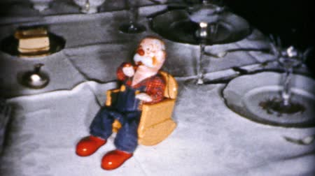 piada : A cute little carving of an old man in a rocking chair blows smoke rings during the Christmas season in Cleveland, Ohio in 1956.