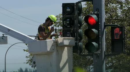 utilidade : A traffic light technician carefully repairs a broken signal light by replacing the old bulbs with new ones in the city of Vancouver, BC.