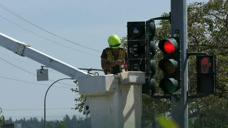 lineman : A traffic light technician carefully repairs a broken signal light by replacing the old bulbs with new ones in the city of Vancouver, BC.