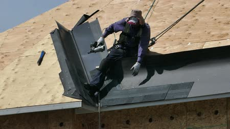 zastřešení : A roofing technician or roofer works hard on a hot summers day to finish shingling a new home in the suburbs of Vancouver, BC, Canada.