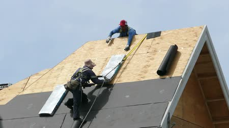 zastřešení : Roofing technicians or roofers work hard on a hot summers day to finish shingling a new home in the suburbs of Vancouver, BC, Canada.