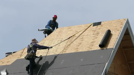 tető : Roofing technicians or roofers work hard on a hot summers day to finish shingling a new home in the suburbs of Vancouver, BC, Canada.