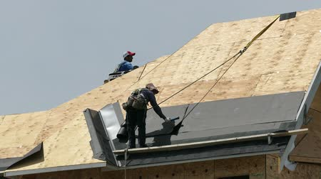 Roofing technicians or roofers work hard on a hot summers day to finish shingling a new home in the suburbs of Vancouver, BC, Canada.
