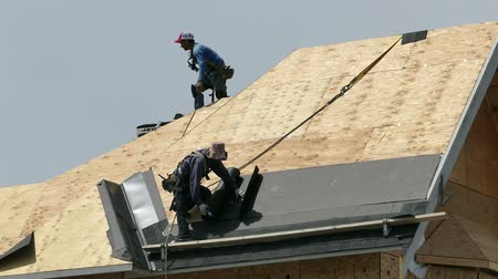 stavitel : Roofing technicians or roofers work hard on a hot summers day to finish shingling a new home in the suburbs of Vancouver, BC, Canada.