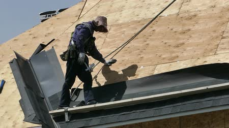çatılar : A roofing technician or roofer works hard on a hot summers day to finish shingling a new home in the suburbs of Vancouver, BC, Canada.